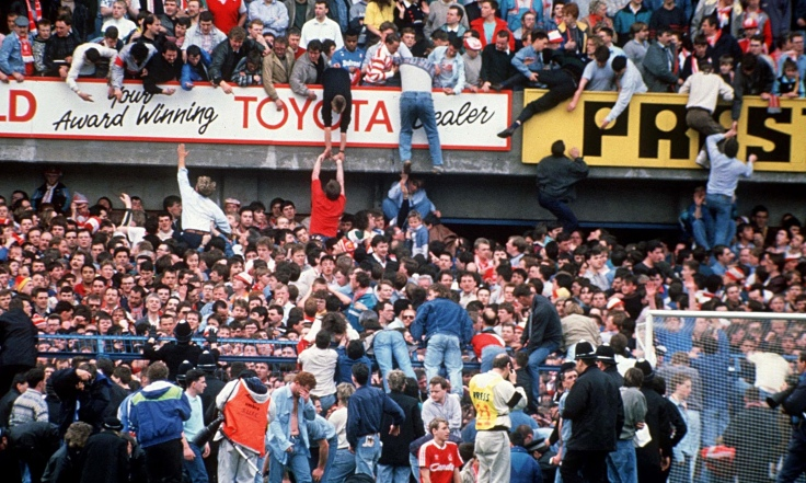 Supporters op de bovenste ring proberen mensen uit de mensenmassa op de onderliggende terraces te bevrijden